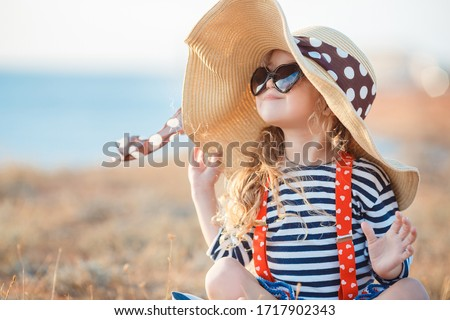 Pretty little girl in a striped dress and hat relaxing on the beach near sea, summer, vacation, travel concept. smiling cute little girl on beach vacation. Baby girl in hat and sun glasses on beach #1717902343