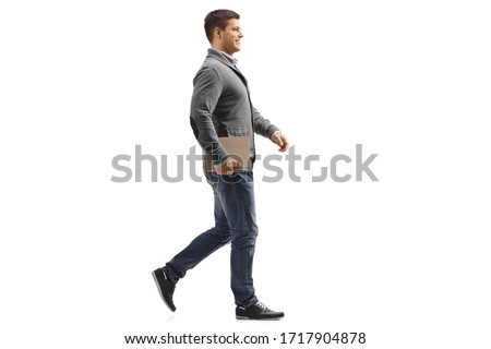 Full length profile shot of a man holding a book and walking isolated on white background #1717904878