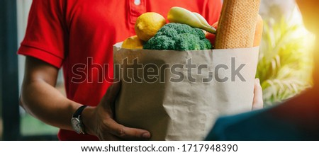 wide panoramic banner of woman customer receiving fresh food set bag from food delivery service man with protection face mask in red uniform at door home, express delivery and food delivery concept #1717948390