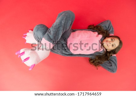 Rabbit totem is symbol of luck. Relaxing on floor top view. Rest and relax. Cute bunny kid. Baby animal character. Girl in bunny costume. Child rabbit kigurumi. Happy girl bunny pajamas. Smiling kid.