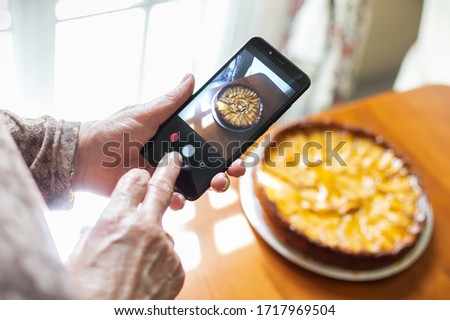 Hands of an old woman taking a photo of freshly baked apple cake with a smartphone at home to share it on social networks. Concept of old people and internet.