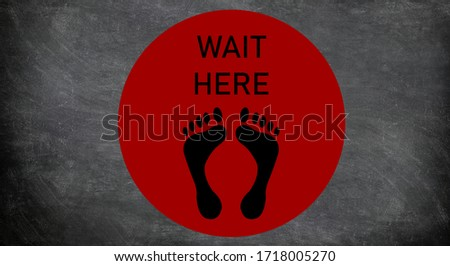 Social distancing sign at supermarket waiting circle for standing on distance in line at cash register. COVID-19 Coronavirus message to stay away from people. Red round with feet drawing and text.