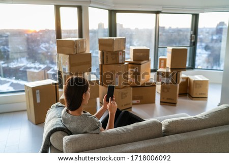 Home move out of apartment moving boxes woman using online movers services on mobile phone app easy pick-up with packages for new home. Asian new homeowner girl happy sitting in sofa. #1718006092