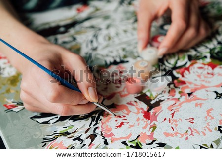 Paint by number concept. Female hands coloring canvas with picture of flowers. Creative hobby. Leisure activity at home during self-isolation COVID-19
