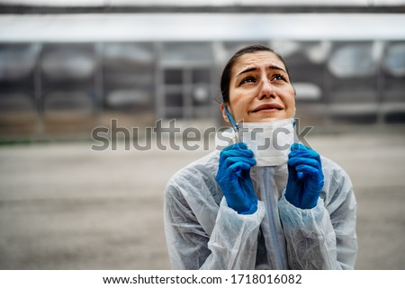 Exhausted crying doctor/nurse in coronavirus protective gear N95 mask.Covid-19 pandemic outbreak.Fatalities grief.Frontline worker mental stress,burnout.Face mask scars.Overworked healthcare provider #1718016082