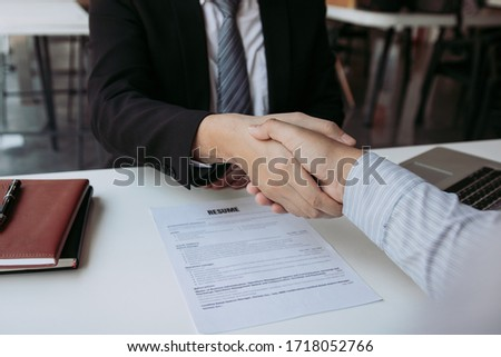 Manager and employee interview concept with handshake after talking about contract signing. Royalty-Free Stock Photo #1718052766