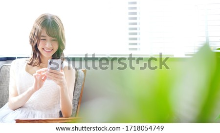Young asian woman using a smart phone. Royalty-Free Stock Photo #1718054749