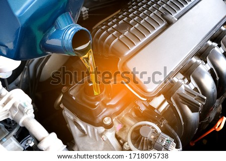 Refueling and pouring oil quality into the engine motor car Transmission and Maintenance Gear .Energy fuel concept. #1718095738