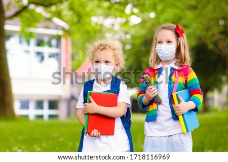 School child wearing face mask during corona virus and flu outbreak. Boy and girl going back to school after covid-19 quarantine and lockdown. Group of kids in masks for coronavirus prevention.  #1718116969
