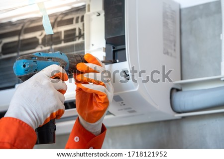 A young Asian air conditioner technician or air-conditioning installation technician is about to repair air conditioning in homes and buildings. Royalty-Free Stock Photo #1718121952