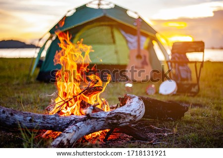 Camping bonfire surrounded by team of asian climbers hiker, they are playing music together in the forest path autumn season. Hiking, hiker, team, forest, camping , activity concept. #1718131921