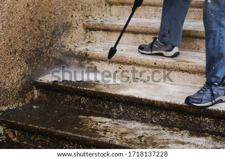 House maintenance : a manual worker cleans and defoams a dirty exterior stone staircase with the lance of a high-pressure washer, while the bad water, charged with moss, trikles down the steps Royalty-Free Stock Photo #1718137228