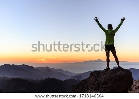 Woman successful hiking or climbing in mountains, motivation and inspiration in beautiful sunset landscape. Female hiker with arms up outstretched on mountain top looking at view. Royalty-Free Stock Photo #1718146564