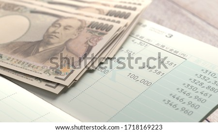 """A Japanese bankbook marked """"deposit"""" and a Japanese bill marked """"10,000 yen #1718169223"""