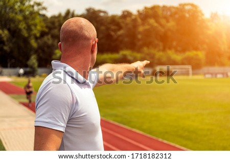Rear view of an bald caucasian man standing on a football field pointing to somewhere. #1718182312