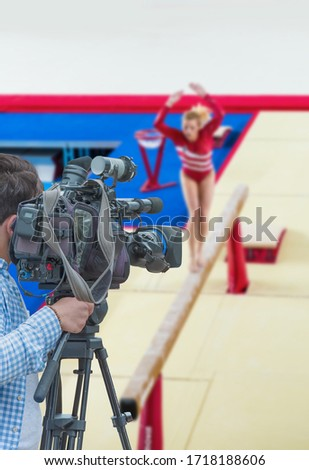 Cameraman shooting live broadcast from gymnastics game to television and internet on the background blured Unidentified women gymnast