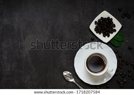 Coffee cup and beans on old kitchen table. Top view with copyspace for your text.