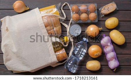 Textile bag with different food on dark wooden background. Food supplies, bread, fruit, vegetables, pasta, eggs, canned food, cookies. Food stock. Quarantine, isolation. Safe home delivery.