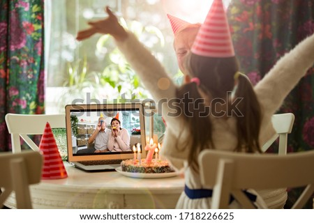 Happy little girl celebrating birthday at home with parents and grand parents on video call. Laptop with senior couple online, cake with candles on table. #1718226625