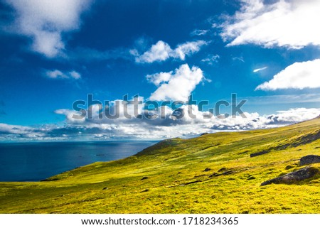 windy and sunny day in norway during summer on lofoten island with blue sea and green meadows #1718234365