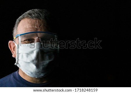 Man with protective medical mask and protective goggles. Coronavirus Covid-19 outbreak, flu contamination and healthcare concept #1718248159