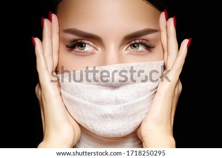 Beautiful woman with bandage mask on face. Fashion eye make-up, long eyelashes and perfect shade eyebrows. Beauty plastic surgery or protection hygiene in viral covid-19 pandemic #1718250295