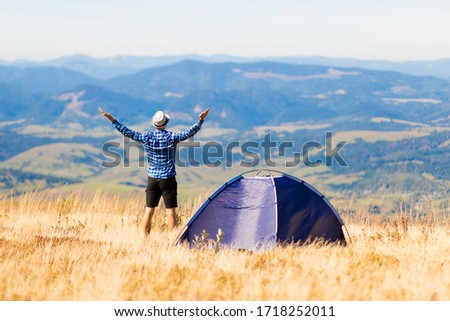 Back view of happy traveler man on top of mountain raised hands enjoying freedom and view near tent camping outdoor. Travel adventure lifestyle success concept, hiking active vacations #1718252011