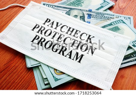 PPP Paycheck Protection Program as SBA loan written on the mask and money. Royalty-Free Stock Photo #1718253064