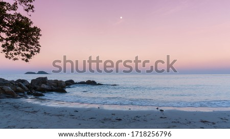 Heavenly peaceful beach in pastel color morning light good for mentally health. The sand beach and calm sea in pastel sunrise morning with a bright star in the sky. No people during pandemic covid19. Royalty-Free Stock Photo #1718256796