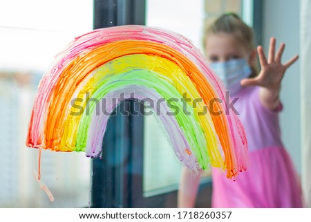 A child in a medical mask looks out the window through a painted rainbow on the glass. The child is out of focus. #1718260357