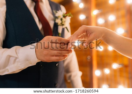 Wedding rings in the hands of the bride and groom. Wearing wedding rings, gentle touches, hands of the bride.  #1718260594
