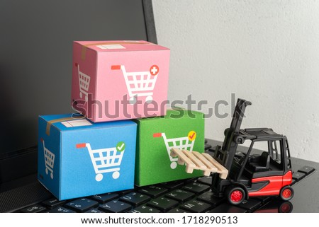 Forklift lift parcel carton box with shopping trolley cart printing on laptop computer white wall background. E-commerce, online shopping, logistic inventory control, cash on delivery (COD) concept.  #1718290513