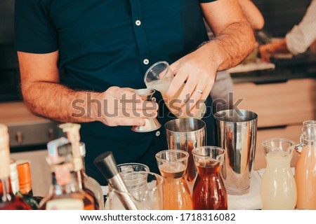The expert bartender is making a cocktail at the home party. Man preparing cocktails. #1718316082