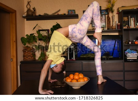 young woman doing yoga exercise. young woman holding blank sign. Coronavirus. children with face mask on quarantine, cooks in the kitchen at home during coronavirus crisis. Stay at home. Enjoy cooking
