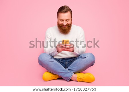Full size photo positive cheerful guy hipster sit floor legs crossed use smart phone typing social network comment wear denim trendy style jeans white jumper isolated pastel color background