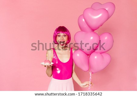 Image of delighted nice woman in wig posing with balloons and cake isolated over pink background