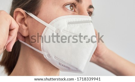 Close up picture of a brunette woman wearing a KN95 FPP2 mask. #1718339941