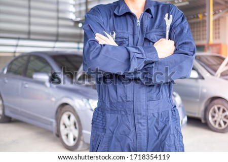 Auto service technician in uniform standing on the background of a car with a screwdriver and repair and maintenance of the car. Garage and car parts replacement concept #1718354119