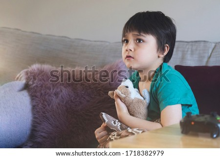 Emotional portrait of kid sitting on sofa hugging his soft toy looking up with worrying face,Child with sad face while watching cartoon on TV, Little boy stay at home relaxing in living room