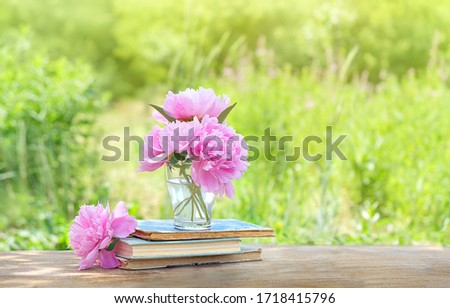 pink peony Flowers and books in summer garden. blossom season,  romantic composition. copy space