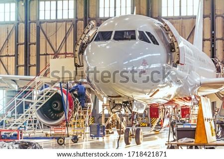 Aviation hangar and repairable passenger aircraft. Work mechanics on maintenance parts Royalty-Free Stock Photo #1718421871