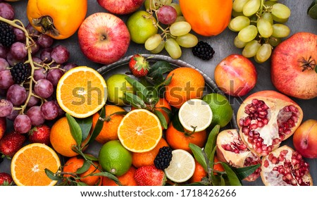 Assorted fruits. Different fruits on a gray background, the whole surface is covered with citrus fruits, pomegranates, apples, grapes, strawberries. Top view #1718426266