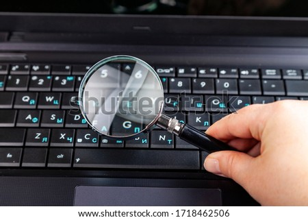 Hand with magnifier on a laptop background. Computer techologies.