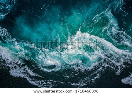 Abstract background. Waves of water of the river and the sea meet each other during high tide and low tide. Whirlpools of the maelstrom of Saltstraumen, Nordland, Norway Royalty-Free Stock Photo #1718468398