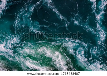 Abstract background. Waves of water of the river and the sea meet each other during high tide and low tide. Whirlpools of the maelstrom of Saltstraumen, Nordland, Norway #1718468407