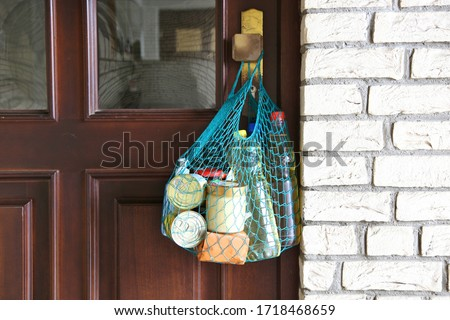delivery groceries during coronavirus infection Covid-19 quarantine. Shopping bag with Merchandise, goods, food hanging at the front door, neighborhood Assistance. helping of vulnerable people concept #1718468659