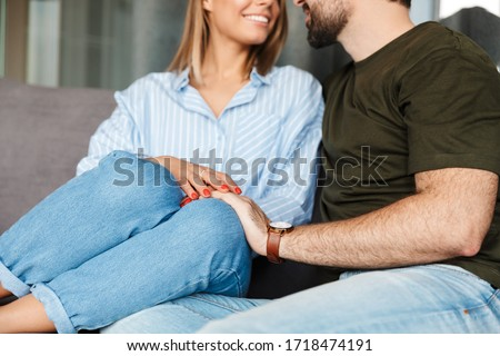 Cropped photo of cheerful caucasian couple smiling and hugging while sitting on sofa at home #1718474191