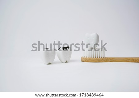 Healthy Tooth on Wooden Brown Toothbrush with Cavity and Decayed Tooth on White Background, If Brush Teeth, Teeth will Good Healthy Royalty-Free Stock Photo #1718489464