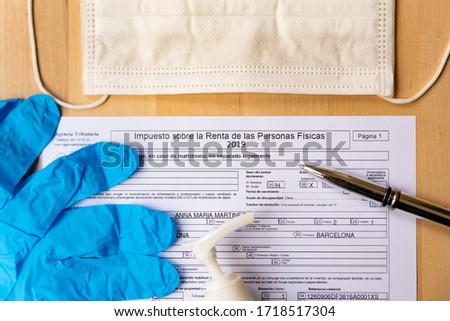 Barcelona, Spain - 20 april 2020: close up of impuesto sobre la renta form for spanish tax declaration with gloves and face mask as a symbol of coronavirus and spanish economy #1718517304