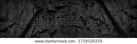 Black and white background. Dark stone grunge background. Mountain texture. Close-up. Wide banner with volumetric rock texture.
